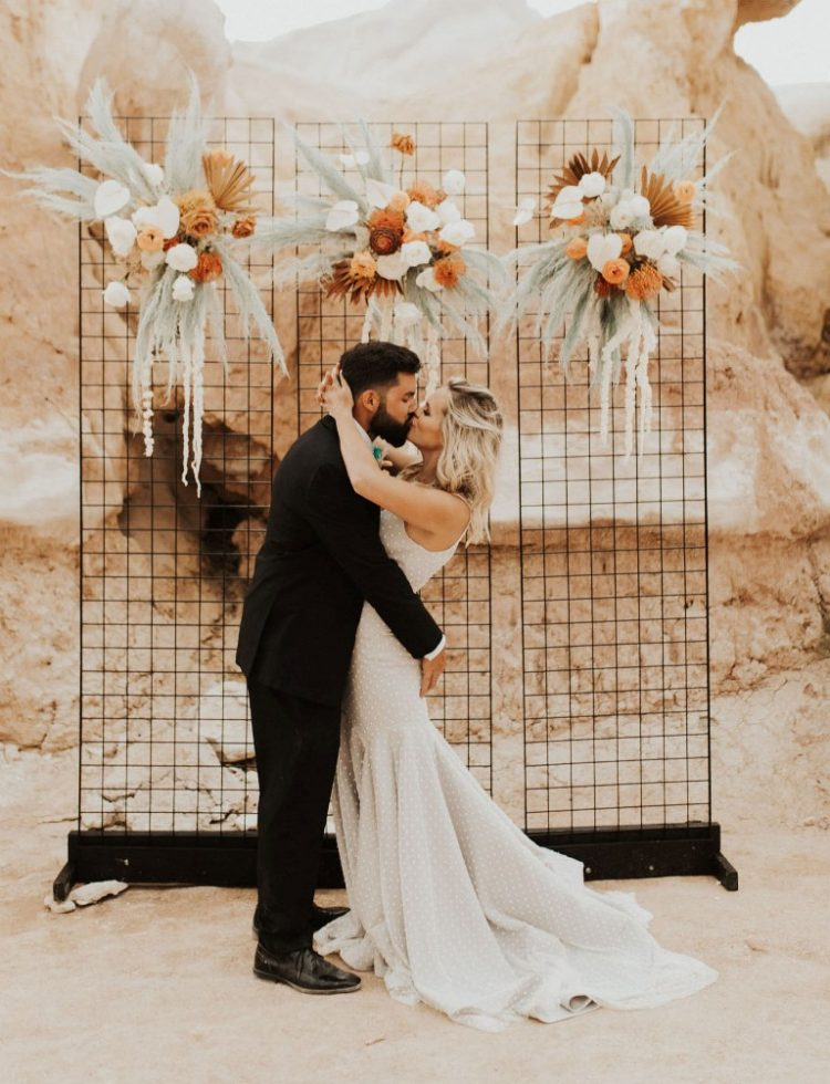 The wedding backdrop was a grid with rust-colored florals and green pampas grass