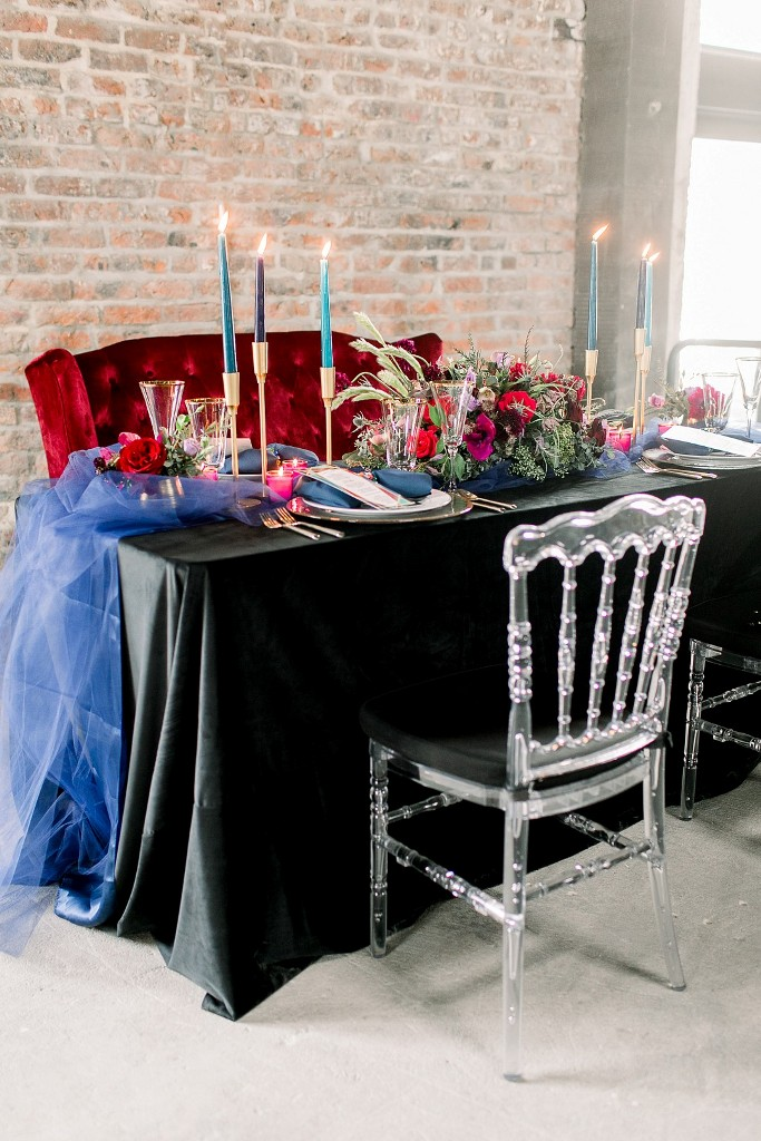 The wedding tablescape was done with jewel-tone candles, a bright table runner, bold blooms and greenery