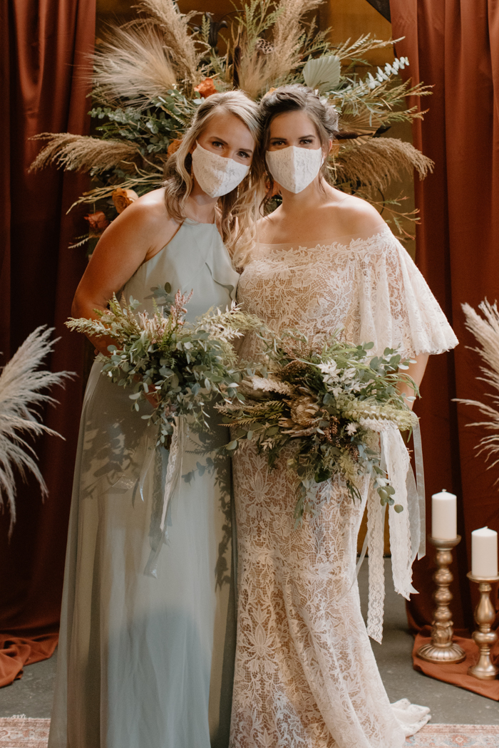 The bridesmaid was wearing a mint halter neckline maxi dress and both girls tried on masks
