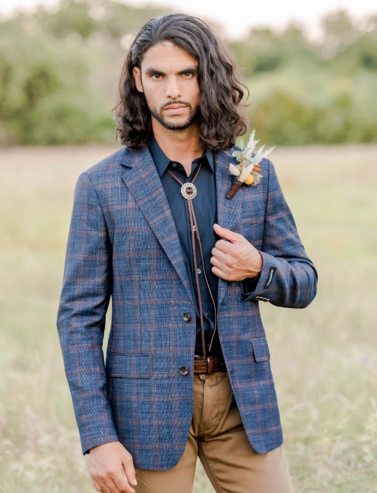 The groom was rocking a black shirt, a navy plaid blazer, tan pants, brown shoes and a bolo tie