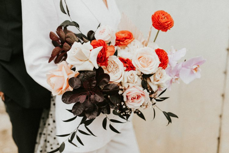 The wedding bouquet was composed of pink roses, red ranunculus, dark foliage