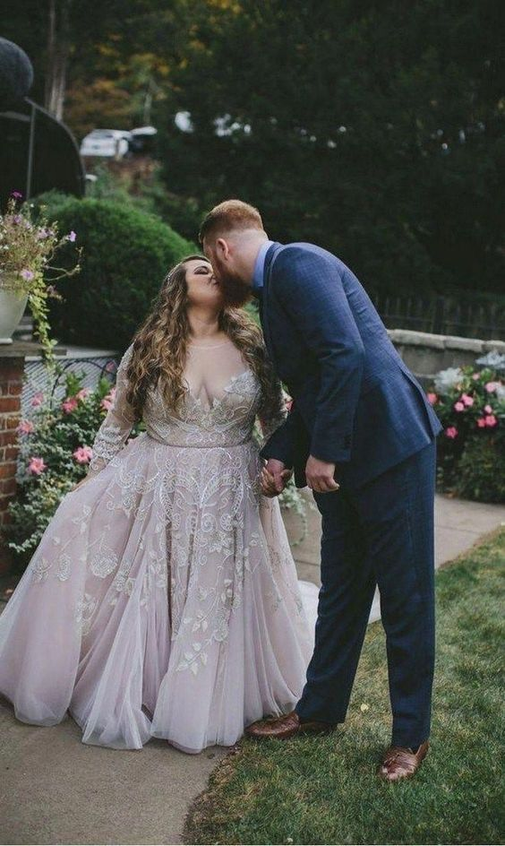 a blush and white wedding ballgown with embroidery and appliques, an illusion neckline and long sleeves