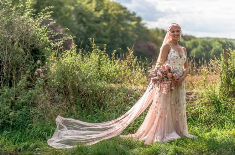 a blush floral applique wedding dress with a V-neckline and a train, a blush veil and pink hair for a pastel bridal look