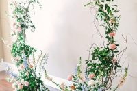 05 a romantic and chic round wedding arch covered with greenery, blush, purple and white blooms and twigs