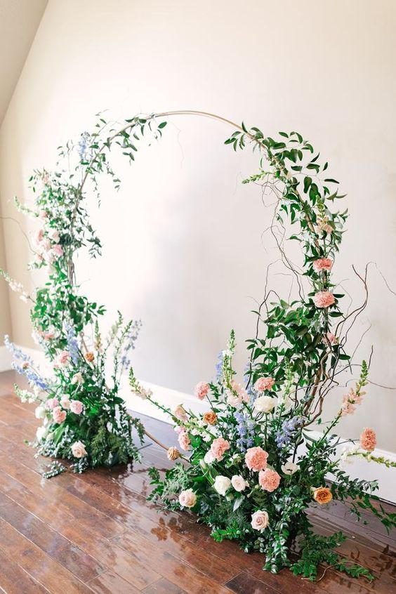 a romantic and chic round wedding arch covered with greenery, blush, purple and white blooms and twigs