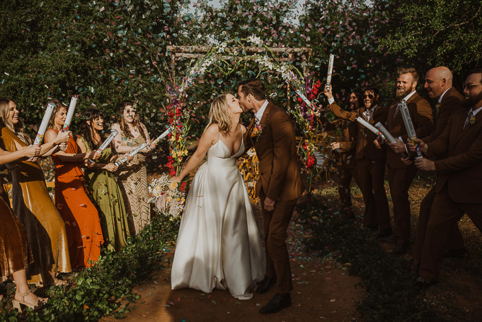 The bridesmaids were wearing mismatching rust, mustard and green dress, and the groomsmen were dressed like the groom