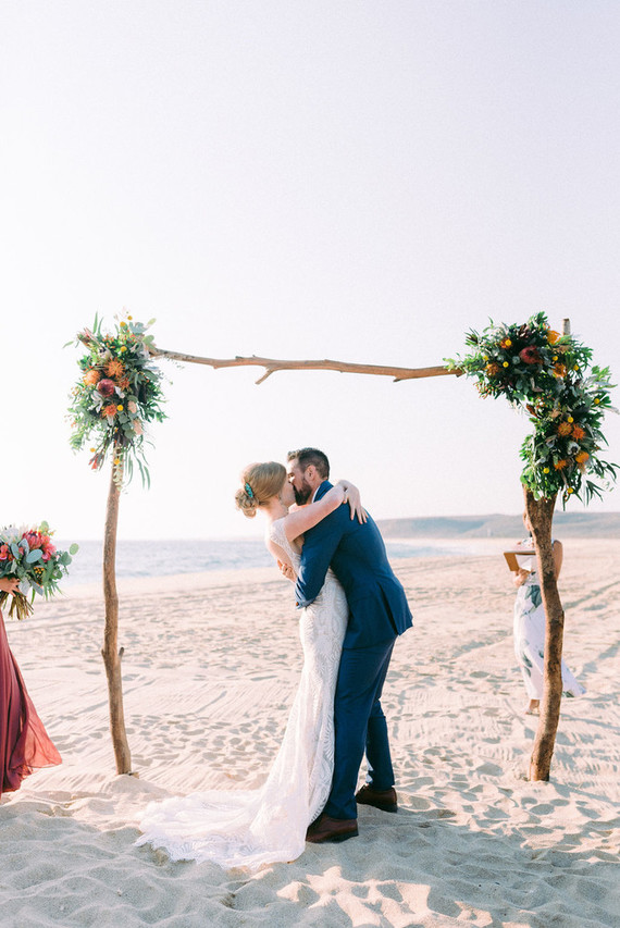 The wedding arch of driftwood was decorated with bright blooms and lush greenery, the sea view was a fantastic backdrop