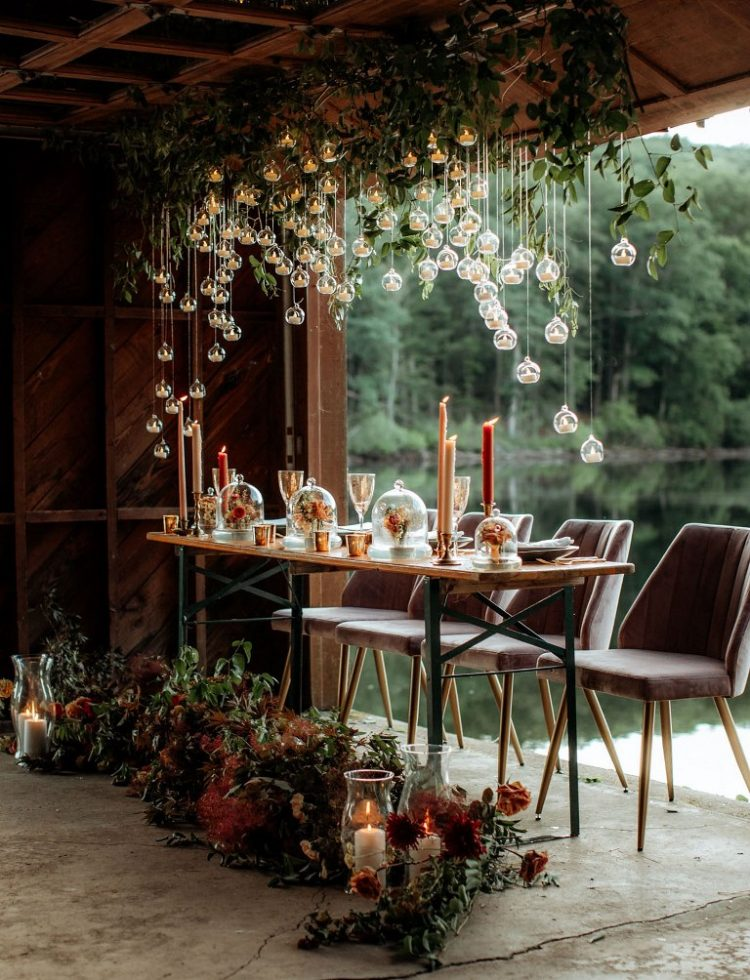 The wedding reception was magical and breathtaking, with lush foliage and hanging candles, bold candles and blooms in cloches