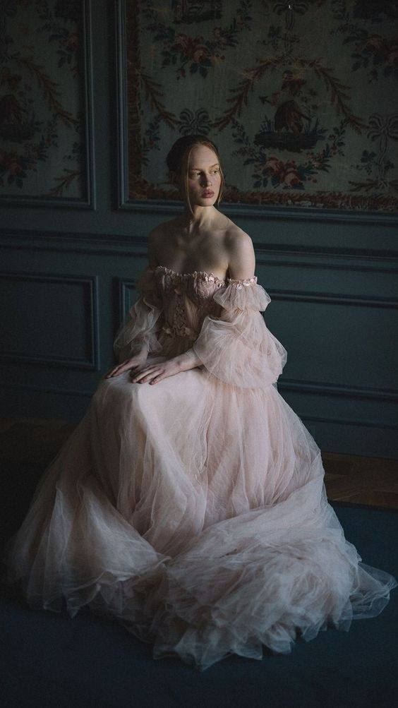 a blush off the shoulder tulle wedding dress with a lace corset and puff sleeves is a very romantic gown