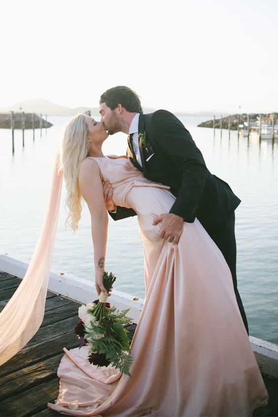 a blush silk sheath wedding dress with a train and a blush veil for a romantic modern bridal look