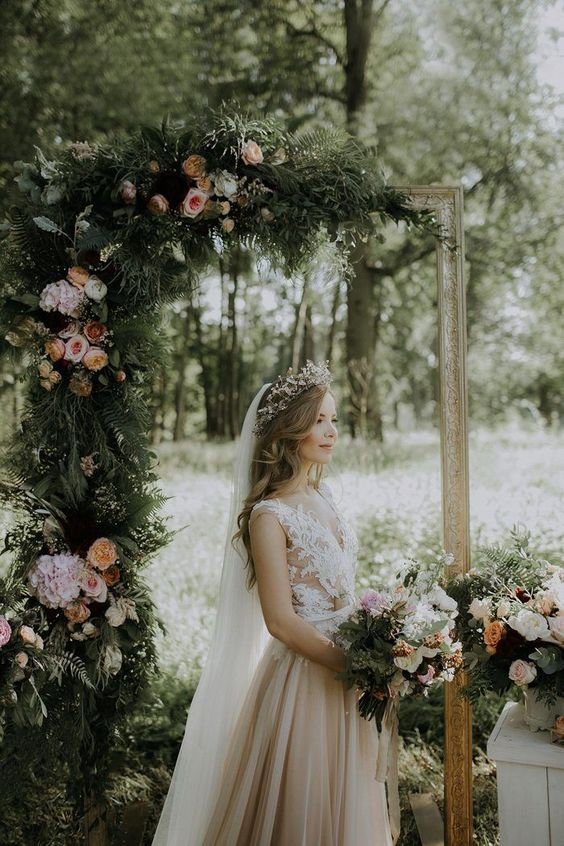 a romantic fairy tale wedding arch of a refined picture frame decorated with greenery and blush blooms is a refined piece