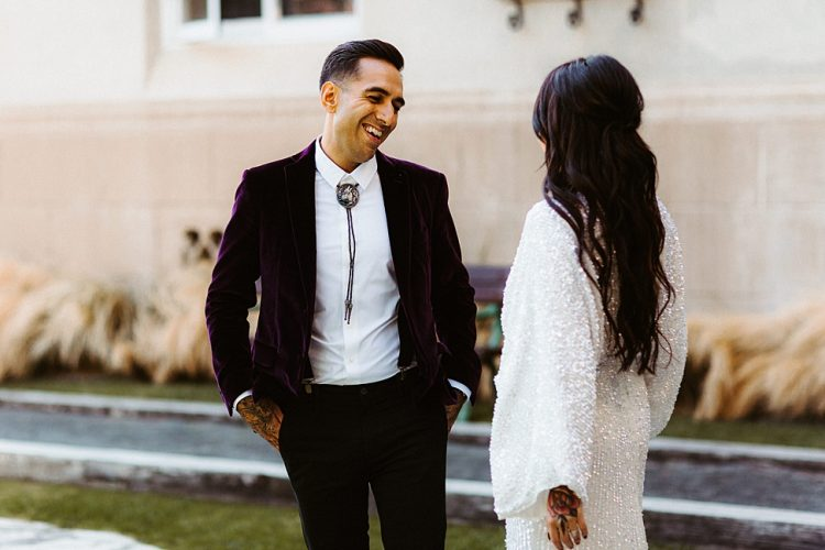 The groom was wearing black pants and suspenders, a bolo tie and a deep purple velvet blazer