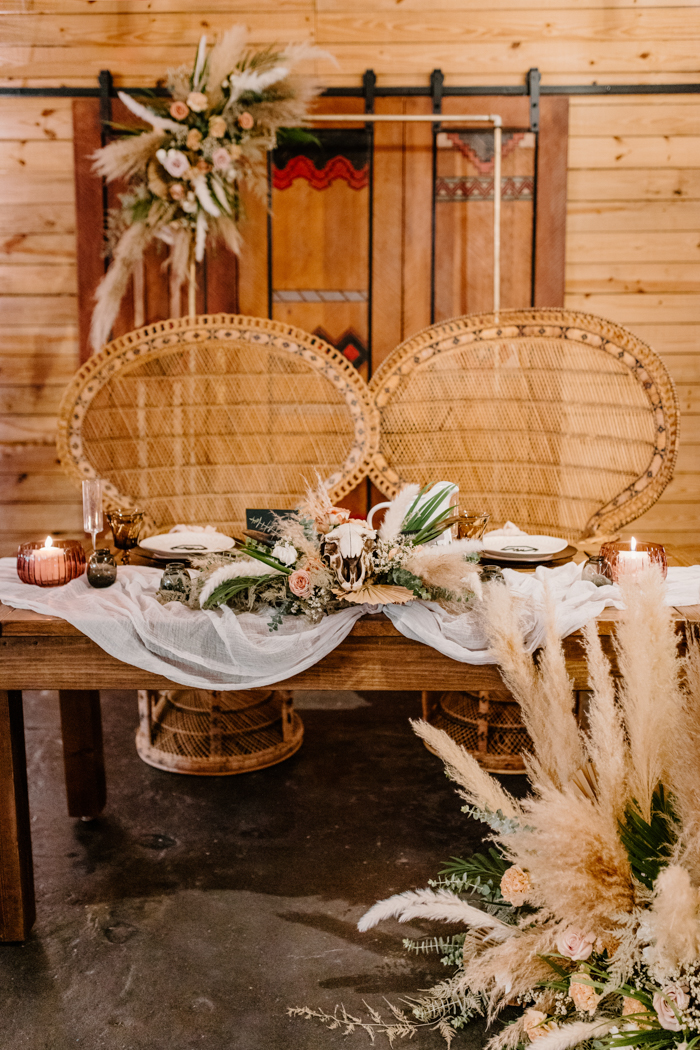 The sweetheart table was decorated with pampas grass, greenery, a skull and pink blooms