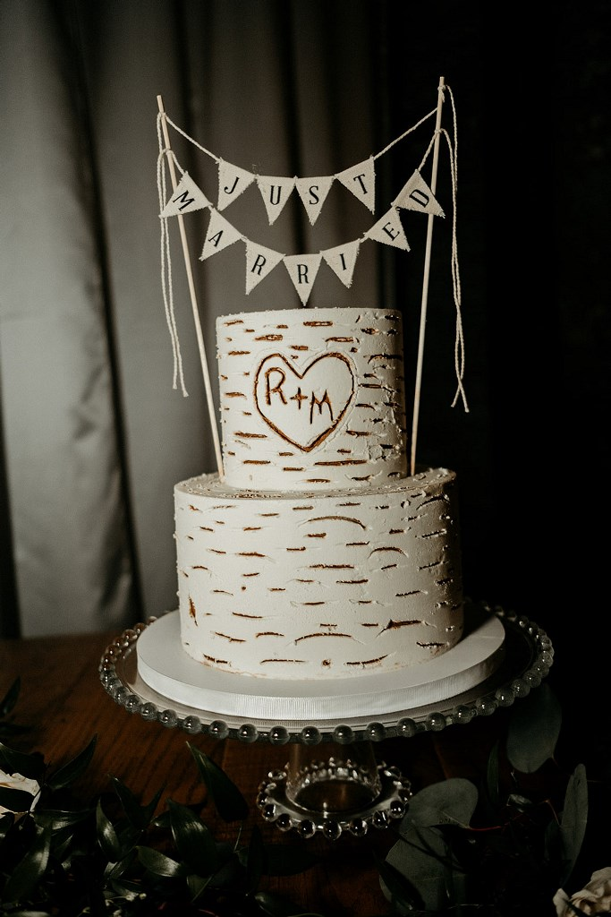 The wedding cake was imitating birch bark for a rustic touch and was topped with a banner