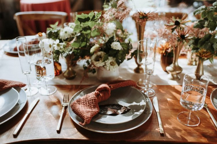 The wedding tablescape was done with rust napkins, neutral and blush blooms and greenery