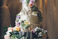 07 a bark wedding cake topped with pastel blooms and greenery and served on a stand with moss, foliage and blooms