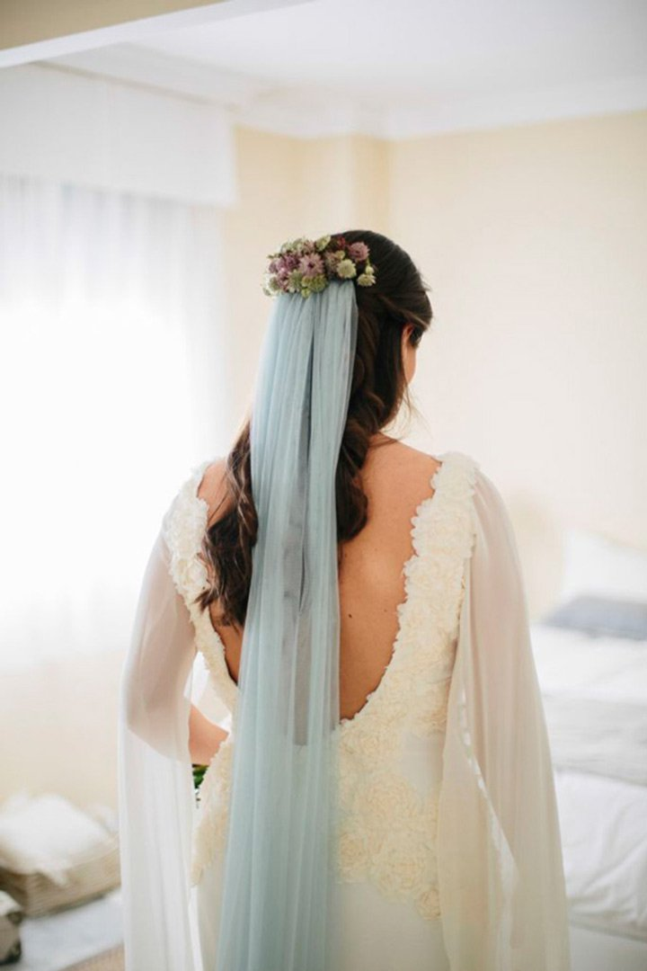 a lace sheath wedding dress with a cutout back and a floral headpiece with a powder blue veil to add a bit of color