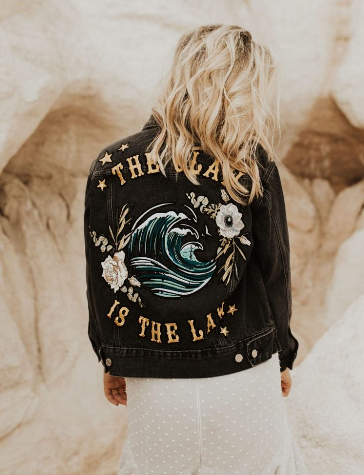 The bride covered up with a black denim jacket with embroidery