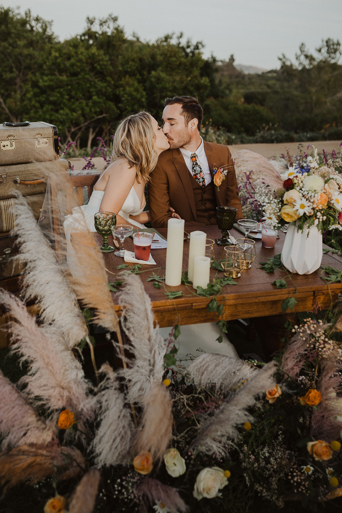 The sweetheart table was done with candles, pampas grass, blooms and greenery