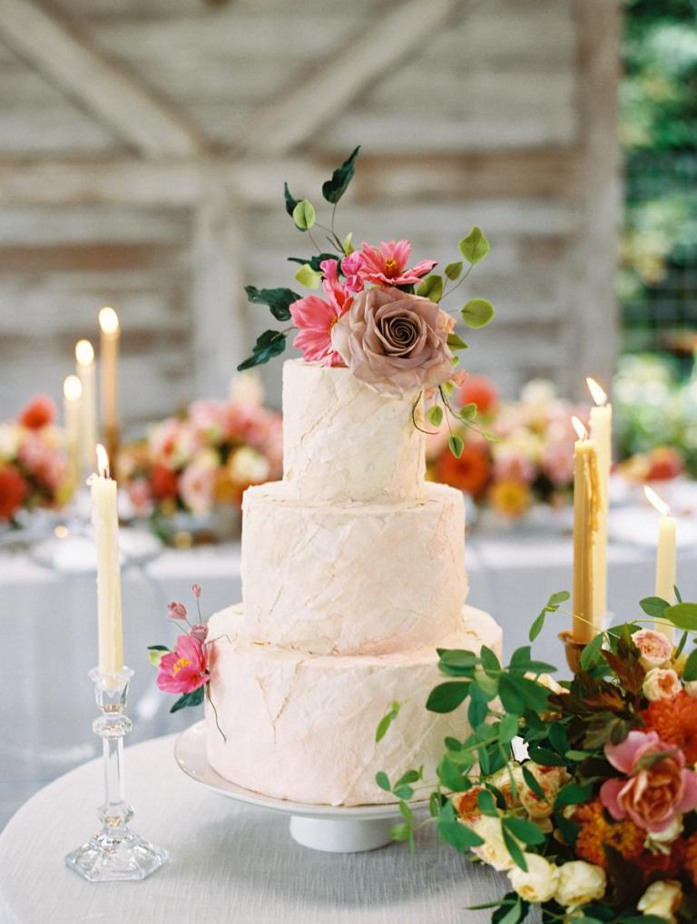 The wedding cake was a textural blush one, with greenery and blooms and candles around