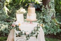 08 a beautiful cake table decorated with greenery, blush blooms, some blush tulle, a gilded frame and a gold covered cake with a calligraphy topper