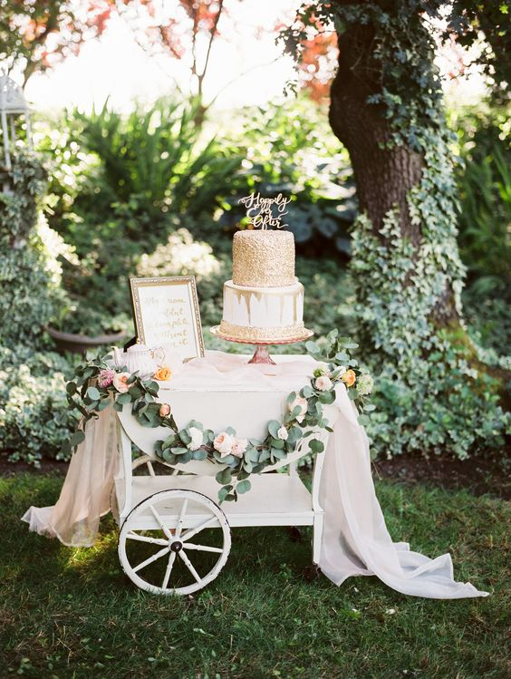 a beautiful cake table decorated with greenery, blush blooms, some blush tulle, a gilded frame and a gold covered cake with a calligraphy topper