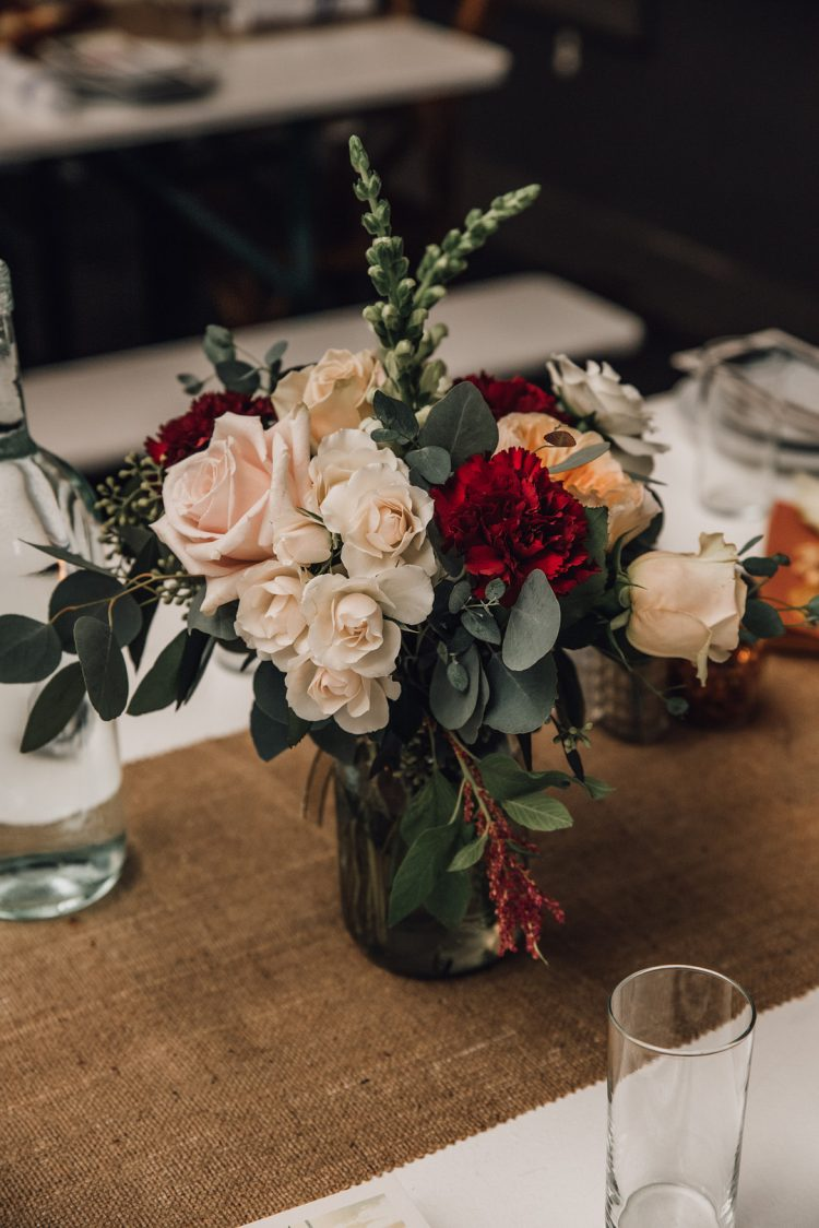 The centerpieces were of blush, burgundy, peachy blooms and greenery, burlap runners added a rustic feel