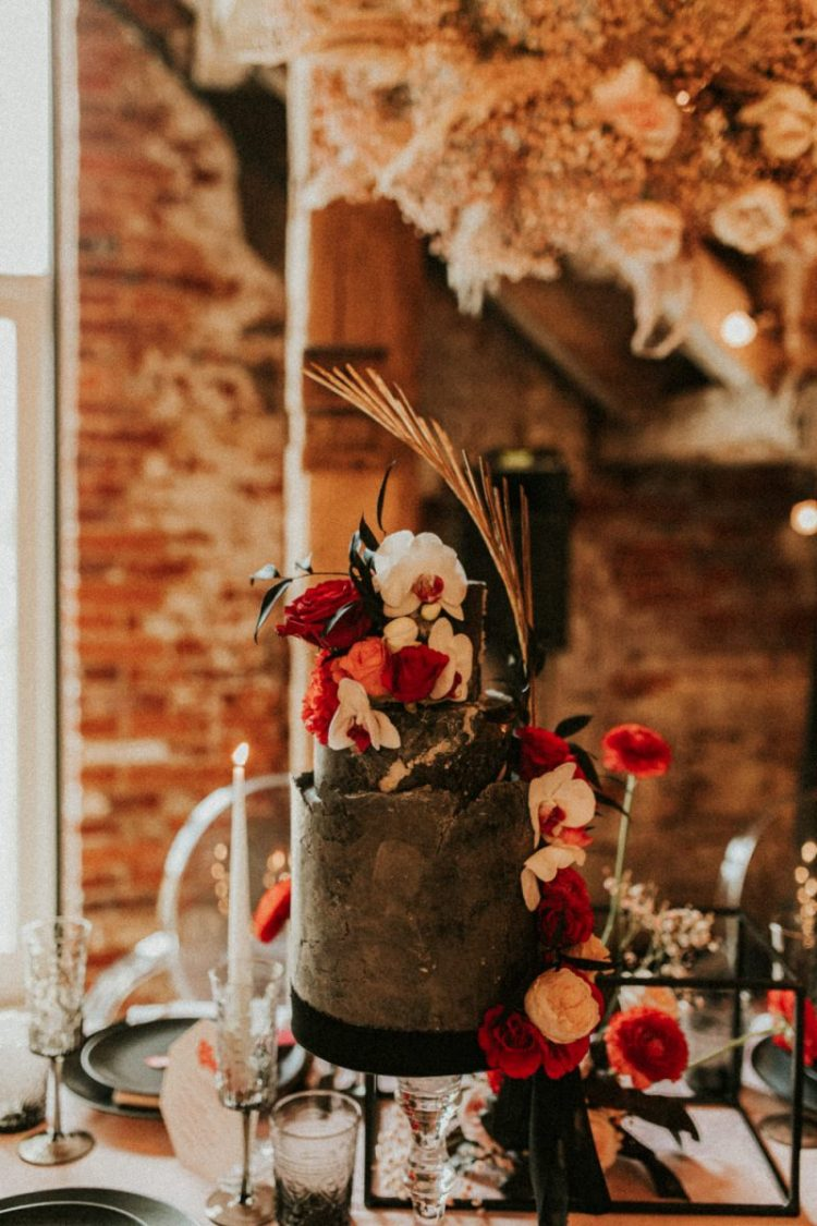 The first wedding cake in black, with a marble effect, red, white and orange blooms