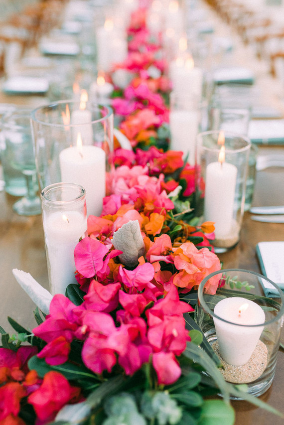 The table decor was done with super bold floral garlands, candles and driftwood