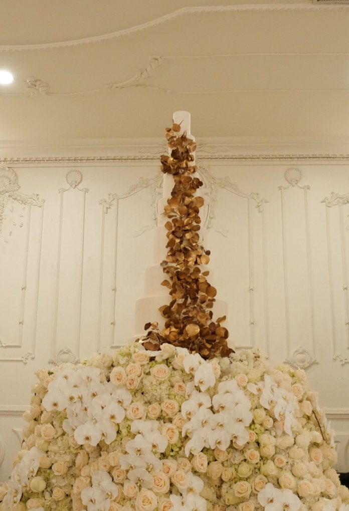 The wedding cake was a white one, decorated with gilded foliage and was palced on a flower covered stand