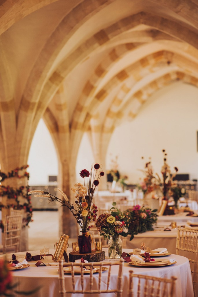 The wedding reception space was done with bright floral arrangements and greenery, pinecones, wood slices and candles