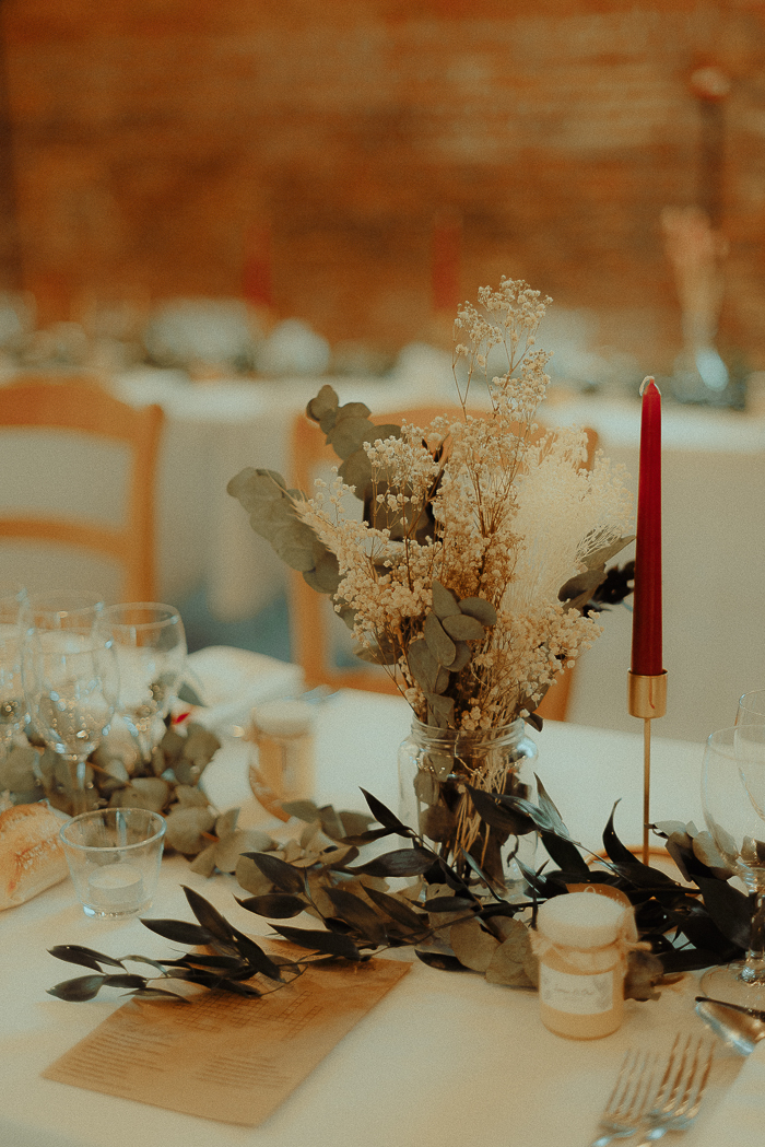 The wedding tablescape was decorated with greenery and dried blooms plus candles