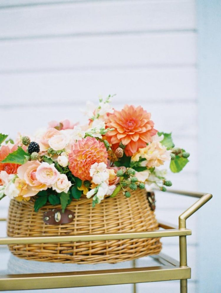 This basket floral arrangement is real essence of summer, with bright and blush blooms, leaves and berries