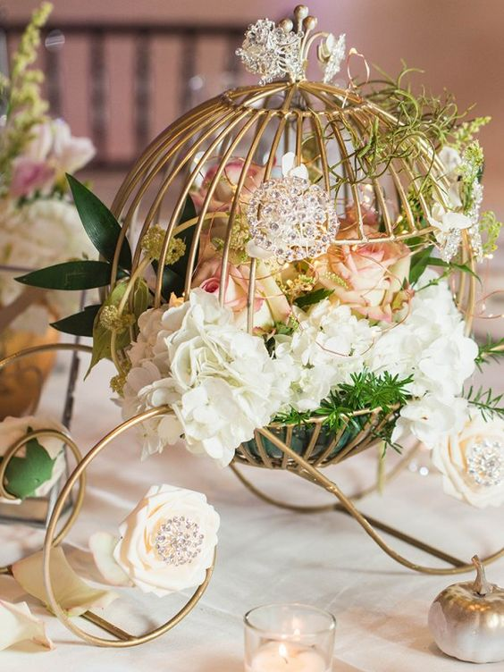 a beautiful fairy tale wedding centerpiece of a wire carriage with blush and white blooms, greenery and candles