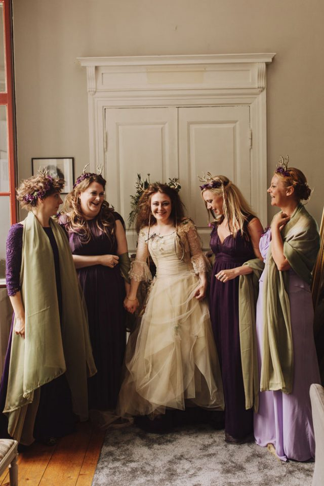 a nude A-line wedding dress with lace sleeves and a bodice, a layered skirt and some greenery and antlers in the hair for a woodland fairy-tale wedding