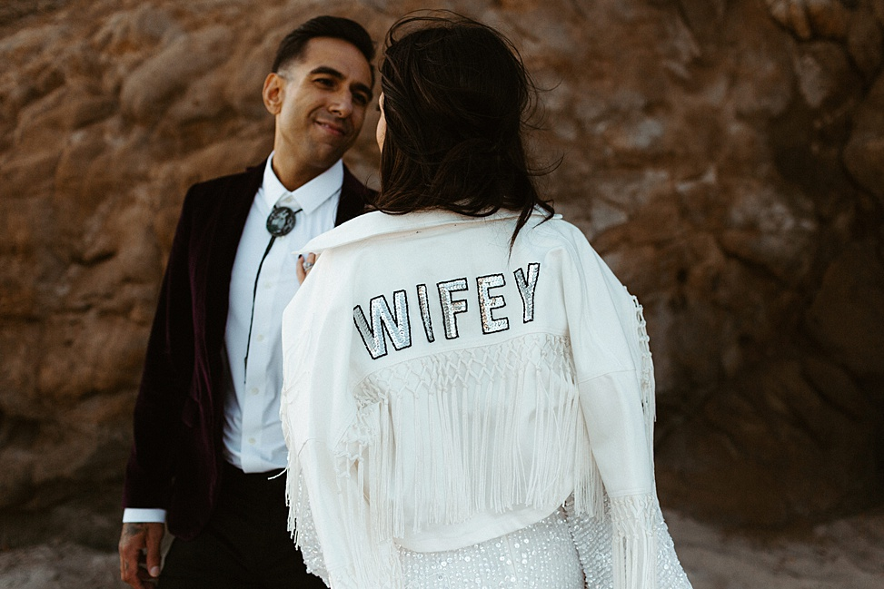 The bride covered up with a white jacket with tassels, macrame and sequin letters
