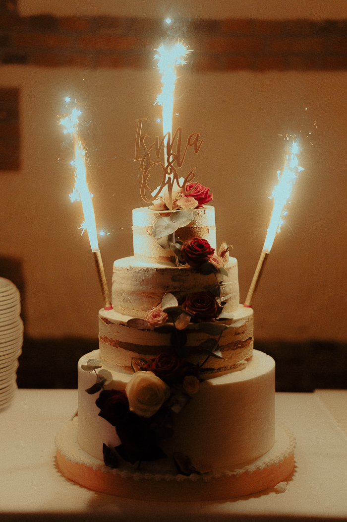 The wedding cake was a naked one, with white and pink blooms, greenery and sparklers