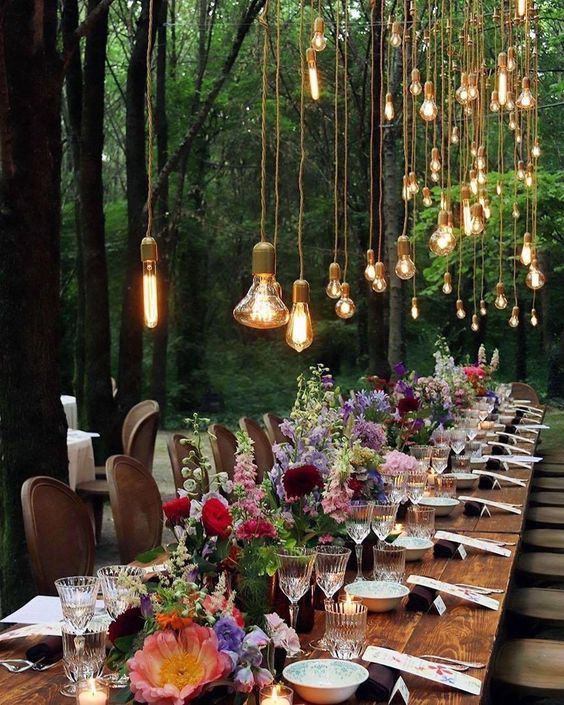 a colorful fairy tale wedding tablescape with lots of bulbs, colorful blooms and candles and some cards