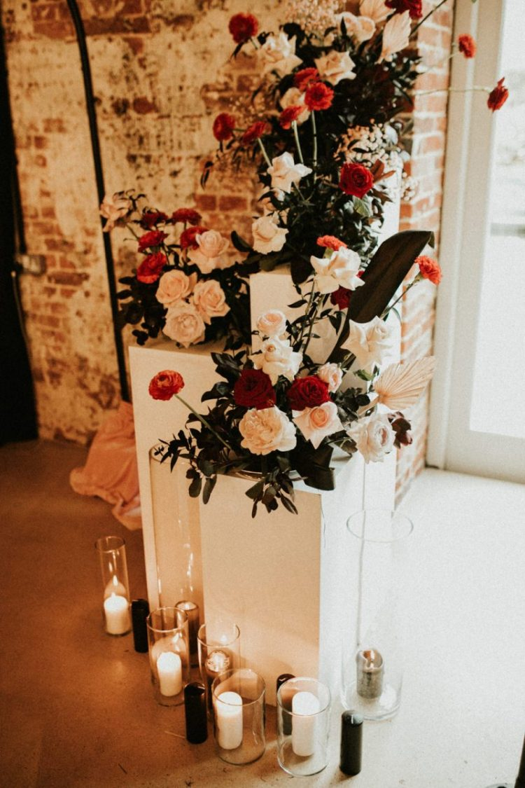 A wedding altar in white, with white and red blooms and black and white candles