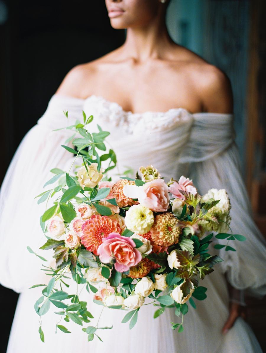 Her wedding bouquet was done with lush greenery, much texture and bright blooms
