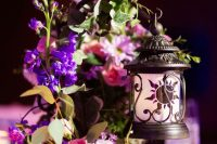 11 a Disney inspired wedding centerpiece of bright and blush blooms, greenery and a candle lantern