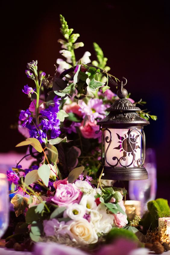 a Disney inspired wedding centerpiece of bright and blush blooms, greenery and a candle lantern