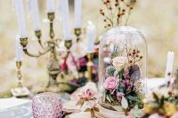 12 a fairy tale wedding centerpiece of a candelabra with candles, blush and pink blooms and leaves, moss and a tree slice