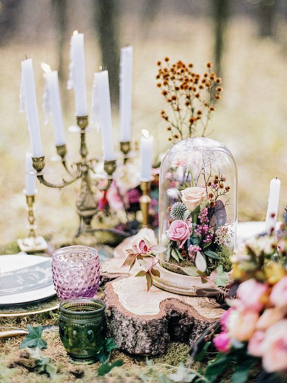 a fairy tale wedding centerpiece of a candelabra with candles, blush and pink blooms and leaves, moss and a tree slice