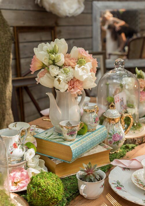 a fairy tale wedding centerpiece of moss, white and blush blooms, teaware and some cards and succulents
