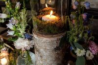 14 a fairy tale wedding centerpiece of purple and white blooms, a candle in moss on a tree stump and greenery around