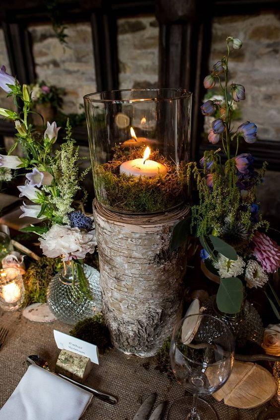 a fairy tale wedding centerpiece of purple and white blooms, a candle in moss on a tree stump and greenery around