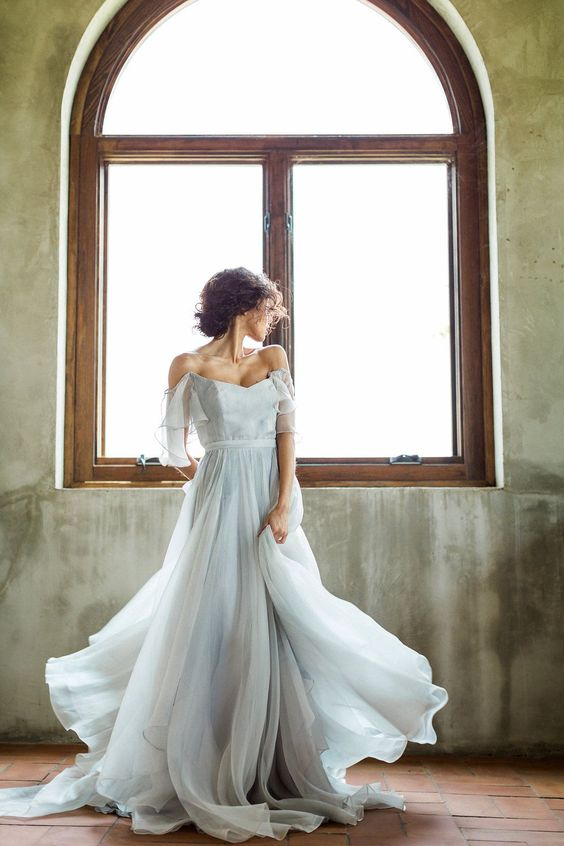a romantic and beautiful powder blue off the shoulder wedding dress with a layered skirt with a train is wow
