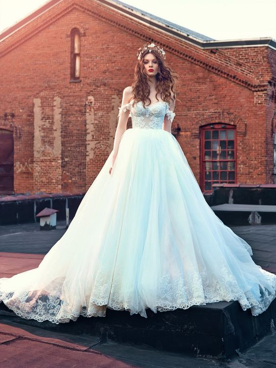 a breathtaking off the shoulder wedding ballgown with a lace bodice and straps, a train and a statement headpiece