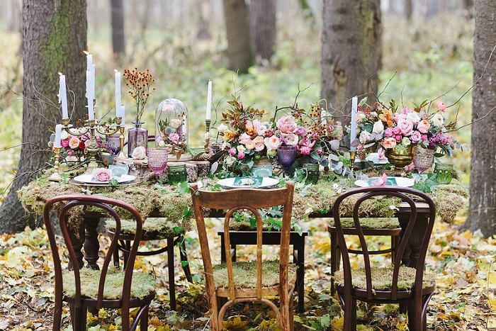 a fairy tale wedding table setting with candles, blush and purple blooms, greenery, moss and colored glasses